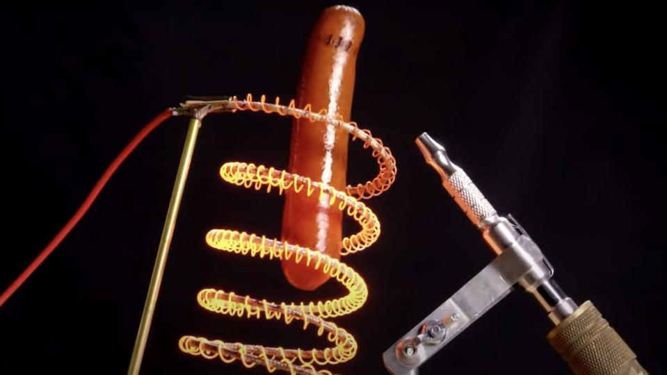 A floating hot dog surrounded by glowing red hot metal coils and an air gun