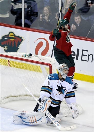 Minnesota Wild's Matt Cullen, top, celebrates a goal by teammate Cal Clutterbuck off San Jose Sharks goalie Thomas Greiss, left, of Germany, in the first period of an NHL hockey game, Sunday, Feb. 26, 2012, in St. Paul, Minn. (AP Photo/Jim Mone)