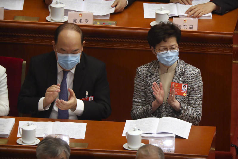 Hong Kong Chief Executive Carrie Lam, right, attends the opening session of China's National People's Congress (NPC) at the Great Hall of the People in Beijing, Friday, May 22, 2020. (AP Photo/Ng Han Guan, Pool)