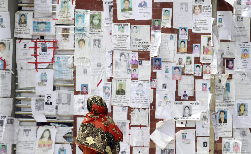 A Bangladeshi woman looks at a wall filled with portraits of missing persons near the site of a garments factory that collapsed last week in Savar near Dhaka, Bangladesh, Friday, May 3, 2013. Authorities suspended the mayor of the suburb of Savar, where the building was located, and arrested an engineer who called for the building's evacuation last week but was also accused of helping the owner add three illegal floors to the eight-story structure. (AP Photo/Ashraful Alam Tito)
