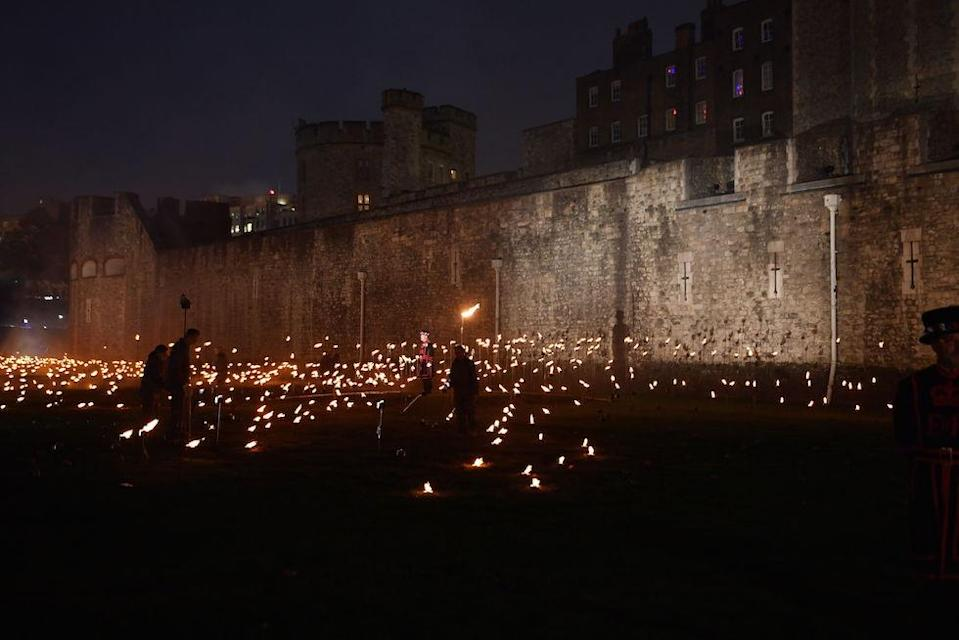<p>Yeoman Warders lighting the first of thousands of flames in a lighting ceremony in the dry moat of the Tower of London as part of an installation called Beyond the Deepening Shadow: The Tower Remembers, to mark the centenary of the end of First World War. (Picture: PA) </p>