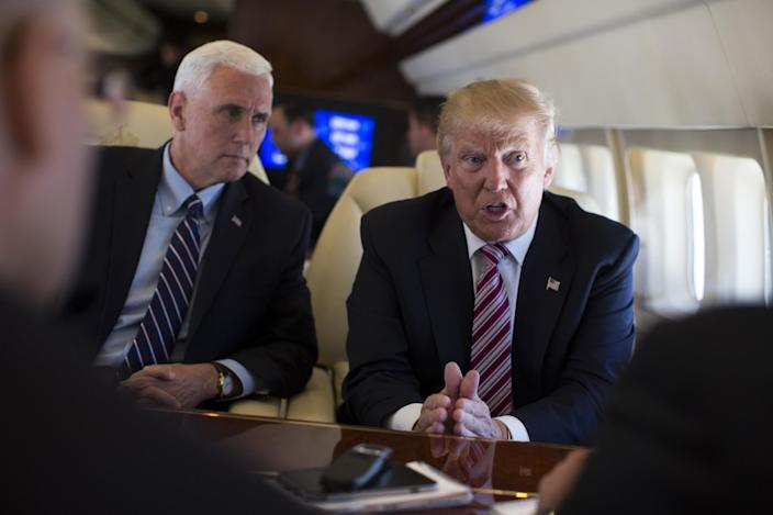 Trump talks with the press on his campaign plane as Pence listens. (Photo: Evan Vucci/AP)