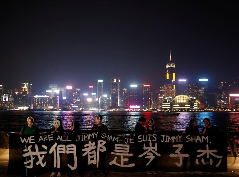 People wearing masks depicting Jimmy Sham hold a banner during an anti-government protest in Hong Kong