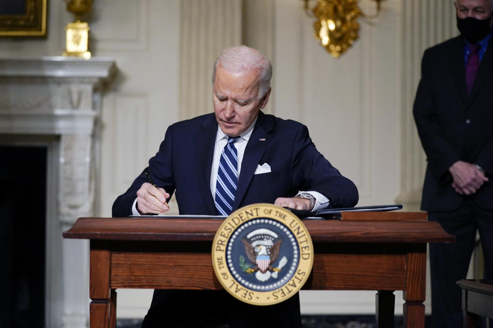 FILE - In this Jan. 27, 2021 file photo, President Joe Biden signs an executive order on climate change, in the State Dining Room of the White House in Washington. Biden is convening a coalition of the willing, the unwilling, the desperate-for-help and the avid-for-money for a two-day summit aimed at rallying the world's worst polluters to do more to slow climate change. Biden's first task when his virtual summit opens Thursday is to convince the world that the United States is both willing and able isn't just willing to meet an ambitious new emissions-cutting pledge, but also able. (AP Photo/Evan Vucci)