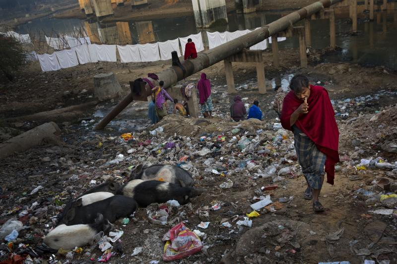 In this Dec. 12, 2014 file photo, an Indian man brushes his teeth using a neem, or native Indian tree, stick as others attend to their morning chores next to a sewage canal before they leave for work early morning in New Delhi, India. (AP Photo/Bernat Armangue, File)