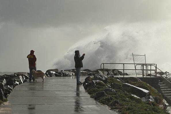 A man takes footage on his phone as a large swell hits the rock groyne at Cottesloe Beach.