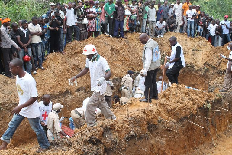 This photo taken on October 20, 2014 in the town of Beni shows people attending a burial after at least 22 people, most of them women and children, were hacked and clubbed to death by Ugandan rebels from the ADF-NALU