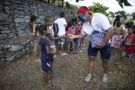 Andres Burgos, a 55-year-old publicist, hands a package of homemade arepas or corn flour patties to a child in Macuto, Venezuela, Saturday Oct. 24, 2020. Burgos rode to the seaside city in Venezuela's La Guaira state, accompanied by other cyclists to distribute the arepas to needy children, adults and the elderly. (AP Photo/Ariana Cubillos)