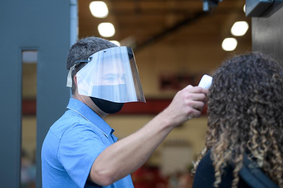 Eighth grade science teacher Jeff Lakey does temperature checks as students arrive at Maryville Junior High School in Maryville, Tenn. on July 31.