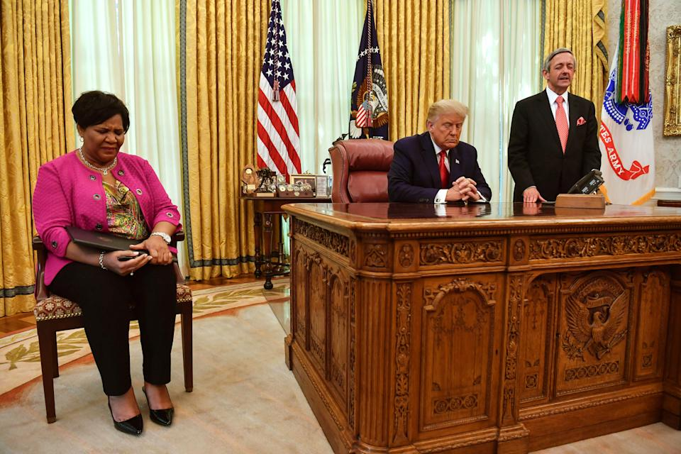 (L-R) Alice Johnson, US President Donald Trump and Pastor Robert Jeffries pray in the Oval Office of the White House in Washington, DC, on August 28, 2020. (Nicholas Kamm/AFP via Getty Images)