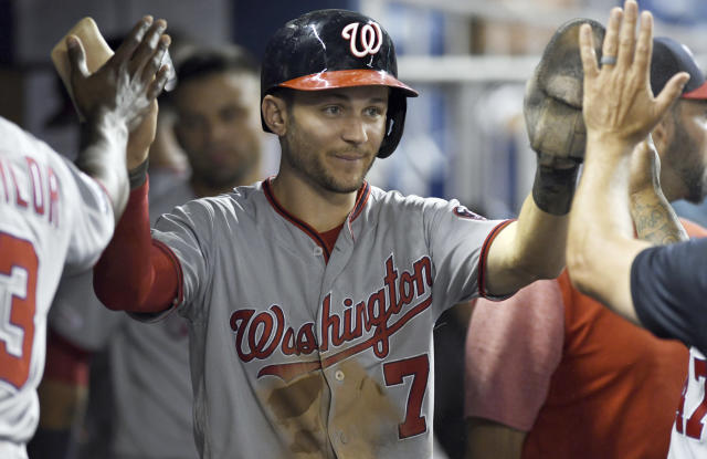 Washington Nationals' Trea Turner is congratulated by teammates after scoring against the Miami Marlins during the ninth inning of a baseball game Wednesday, June 26, 2019, in Miami. (AP Photo/Jim Rassol)