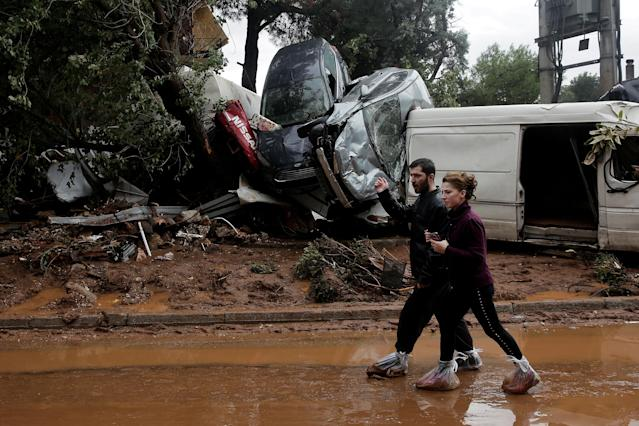 <p>Locals wear plastic bags to protect from mud as they walk next to destroyed cars, following flash floods which hit areas west of Athens on November 15 killing at least 15 people, in Mandra, Greece, Nov. 16, 2017. (Photo: Alkis Konstantinidis/Reuters) </p>