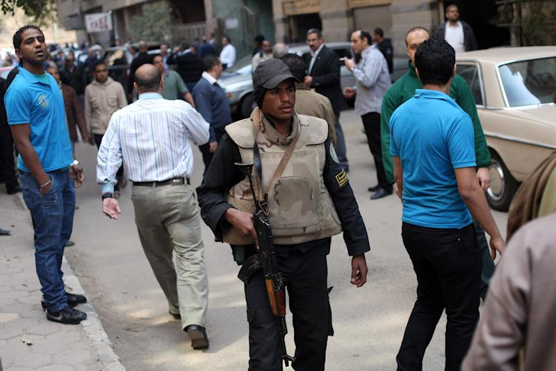 An Egyptian policeman holds a gun, as police officers arrest Ahmed Qaddaf al-Dam, cousin of Libya's former dictator Moammar Gadhafi, not pictured, in Cairo, Egypt, March 19. 2013. Egyptian security forces arrested a cousin of Libya's former dictator Moammar Gadhafi on Tuesday following an hours-long siege of his home in central Cairo, a security official and witnesses said. (AP Photo/Khalil Hamra)