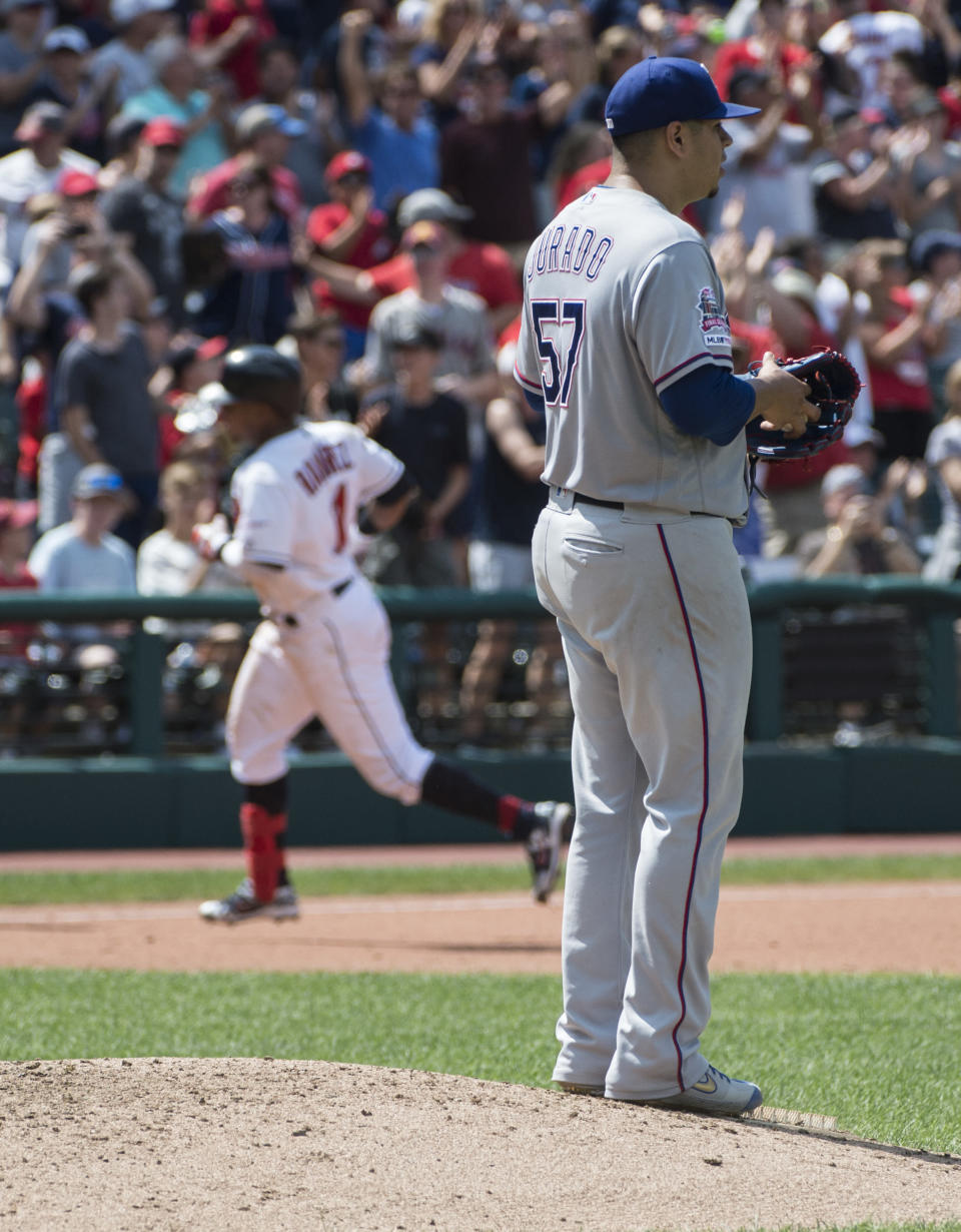 Texas Rangers starting pitcher Ariel Jurado turns away as Cleveland Indians' Jose Ramirez rounds the bases after hitting a two-run home run during the seventh inning of the first game of a baseball doubleheader in Cleveland, Wednesday, Aug. 7, 2019. (AP Photo/Phil Long)