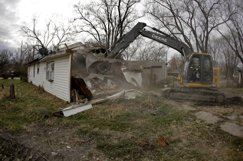 In this photo taken Monday, Nov. 18, 2019, Tim Kates demolishes Tammy Kilgore's former home as part of a voluntary buyout in flood-prone Mosby, Mo. Kilgore accepted a $45,000 payment to leave her home of 38 years and has moved to a nearby community. (AP Photo/Charlie Riedel)