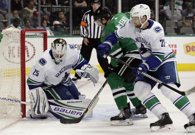 Vancouver Canucks goalie Jacob Markstrom (25) traps a puck beneath his leg pad as defenseman Alexander Edler (23) helps against pressure from Dallas Stars left wing Curtis McKenzie (11) in the first period of an NHL hockey game in Dallas, Sunday, March 25, 2018. (AP Photo/Tony Gutierrez)
