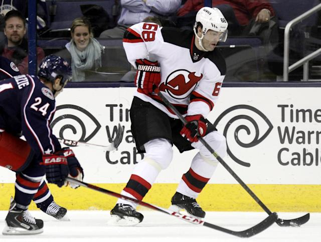 New Jersey Devils' Jaromir Jagr, right, of the Czech Republic controls the puck against Columbus Blue Jackets' Derek MacKenzie during the second period of an NHL hockey game in Columbus, Ohio, Tuesday, Oct. 22, 2013. The Blue Jackets won 4-1. (AP Photo/Paul Vernon)