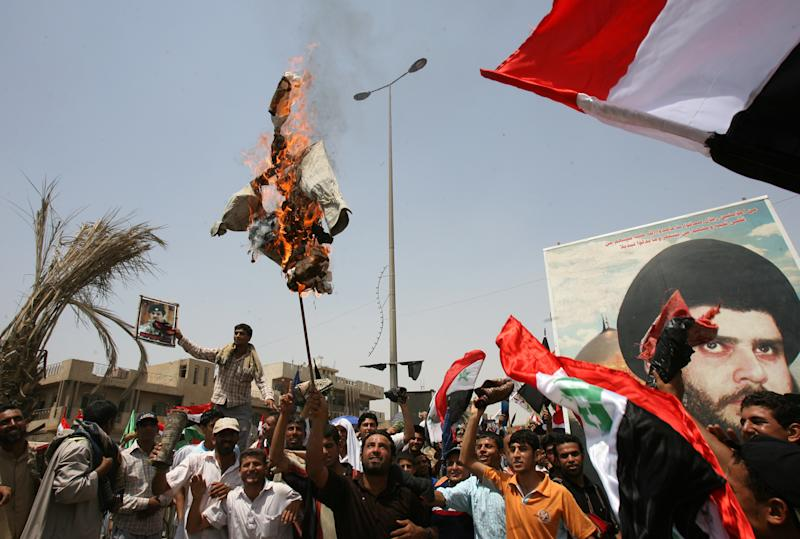 Iraqis burn an effigy of Prime Minister Nuri al-Maliki as the hold up a portrait of anti-American Shiite Muslim cleric Moqtada al-Sadr during a protest in the Sadr City district of eastern Baghdad on May 30, 2008 (AFP Photo/Ali al-Saadi)