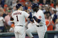 Houston Astros designated hitter Yordan Alvarez, right, is greeted by Carlos Correa near home plate after hitting a solo home run off Chicago White Sox starting pitcher Reynaldo Lopez during the fifth inning in Game 1 of a baseball American League Division Series Thursday, Oct. 7, 2021, in Houston. (AP Photo/David J. Phillip)