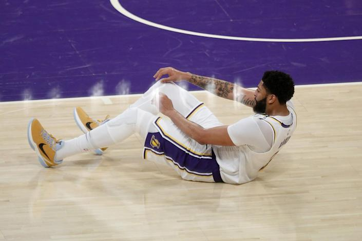 Lakers forward Anthony Davis struggles to get to his feet after injuring his left groin on a driving layup.