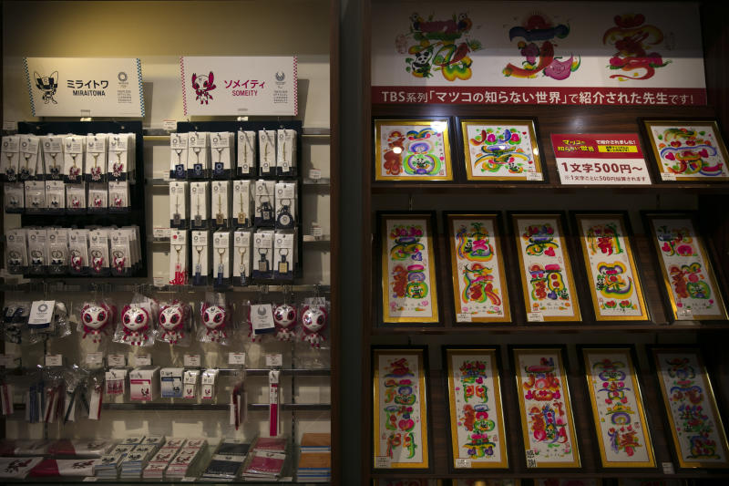 In this Feb. 13, 2020, photo, Tokyo 2020 souvenirs and calligraphy prints are for sale at a gift shop in Yokohama's Chinatown, near Tokyo. A top Olympic official made clear Friday the 2020 Games in Tokyo will not be cancelled despite the virus that has spread from China. (AP Photo/Jae C. Hong)