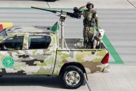 A Turkmenistan army soldier with a shepherd dog Alabay rides a pickup during a military parade celebrating the country's 30th independence anniversary in Ashgabat, Turkmenistan, Monday, Sept. 27, 2021. The pomp-filled parade took place in Ashgabat, the capital of the gas-rich former Soviet nation in Central Asia. Aside from troops and military equipment, the parade featured employees of state ministries and institutions demonstrating their achievements and Alabai dogs, which accompanied soldiers on military vehicles. (AP Photo/Alexander Vershinin)