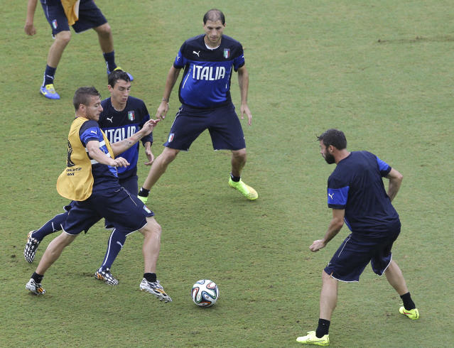 Italy's Ciro Immobile, left, and Matteo Darmian, second from left, vie for control of the ball, as Gabriel Paletta, top, and Andrea Barzagli watch during a training session, a the day before their group D World Cup soccer match, at the Arena das Dunas in Natal, Brazil, Monday, June 23, 2014. (AP Photo/Antonio Clanni)