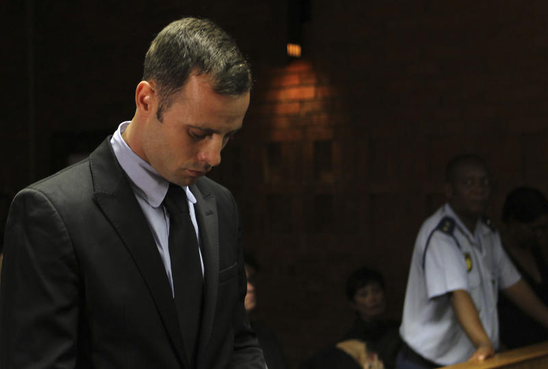 """Olympic athlete Oscar Pistorius stands inside the court as a police officer looks on during his bail hearing at the magistrate court in Pretoria, South Africa, Wednesday, Feb. 20, 2013. A South African judge says defense lawyers will need to offer """"exceptional"""" reasons to convince him to grant bail for Oscar Pistorius, when a hearing resumes Wednesday. (AP Photo/Themba Hadebe)"""