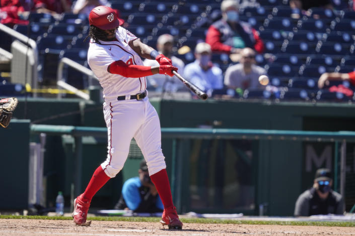 Washington Nationals' Josh Bell hits a three-run double during the fourth inning of a baseball game against the Miami Marlins at Nationals Park, Saturday, May 1, 2021, in Washington. (AP Photo/Alex Brandon)