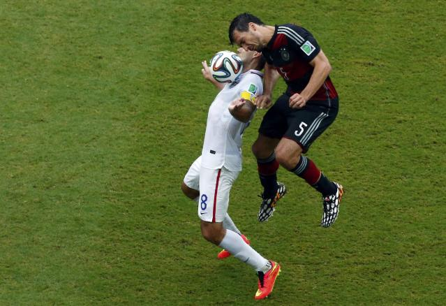 Clint Dempsey of the U.S. jumps for the ball with Germany's Mats Hummels (R) during their 2014 World Cup Group G soccer match at the Pernambuco arena in Recife June 26, 2014. REUTERS/Ruben Sprich (BRAZIL - Tags: SOCCER SPORT WORLD CUP)