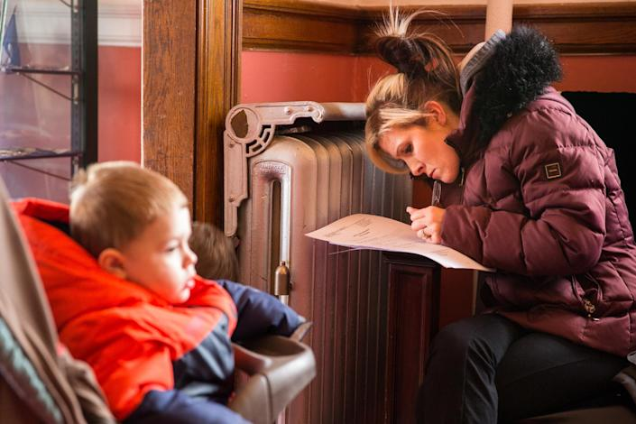 CLICK IMAGE for slideshow: Shantel Bourque, with her son Gage Bourque age 2, fills out paper work before having her children's blood tested for lead on January 23, 2016 at the Masonic Temple in Flint, Michigan. Bourque has lived in the city for four years and didn't know how bad the problem was until four months ago but was using the water regularly until then. Concern for lead poisoning is linked to a federal state of emergency being declared due to the city's water supply becoming contaminated. (Brett Carlsen/Getty Images)