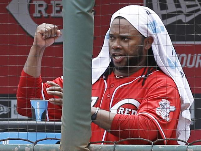 Cincinnati Reds starting pitcher Johnny Cueto clinches his fist in the dugout after relief pitcher Manny Parra got the final two outs in the seventh inning of a baseball game against the Chicago Cubs, Tuesday, July 8, 2014, in Cincinnati. Parra relieved Cueto in the seventh with the bases loaded and one out. Cueto earned his ninth win of the season as Cincinnati won 4-2. (AP Photo/Al Behrman)