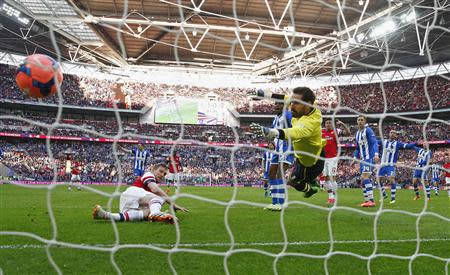 Arsenal's Per Mertesacker (L) heads and scores his goal against Wigan Athletic during their English FA Cup semi-final soccer match at Wembley Stadium in London April 12, 2014. REUTERS/Eddie Keogh