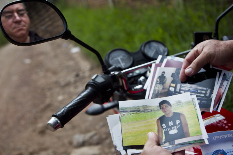 In this Oct 17, 2012 photo, Wilfredo Yanez, reflected on a mirror of his motorcycle, shows pictures of his late son Jaasiel Yanez, 15, at the site where he was shot dead allegedly by soldiers in Tegucigalpa, Honduras. According to his relatives, Jaasiel was killed by soldiers early Sunday, May 27, when he was riding a motorcycle, near a military checkpoint.  (AP Photo/Esteban Felix)