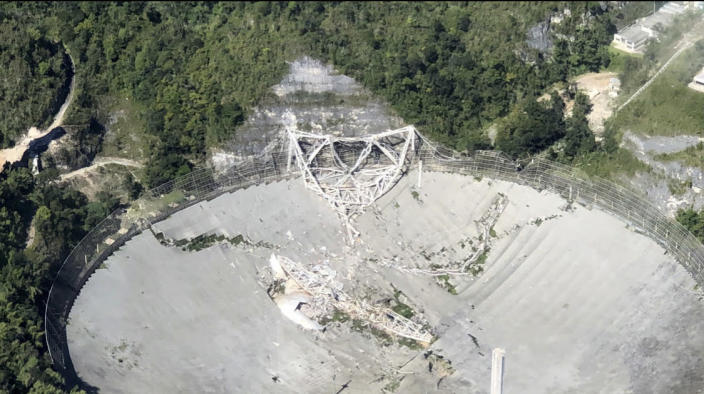 This photo provided by Aeromed shows the collapsed Radio Telescope in Arecibo, Puerto Rico, Tuesday, Dec. 1, 2020. The already damaged radio telescope that has played a key role in astronomical discoveries for more than half a century completely collapsed, falling onto the northern portion of the vast reflector dish more than 400 feet below. (Yamil Rodriguez/Aeromed via AP)