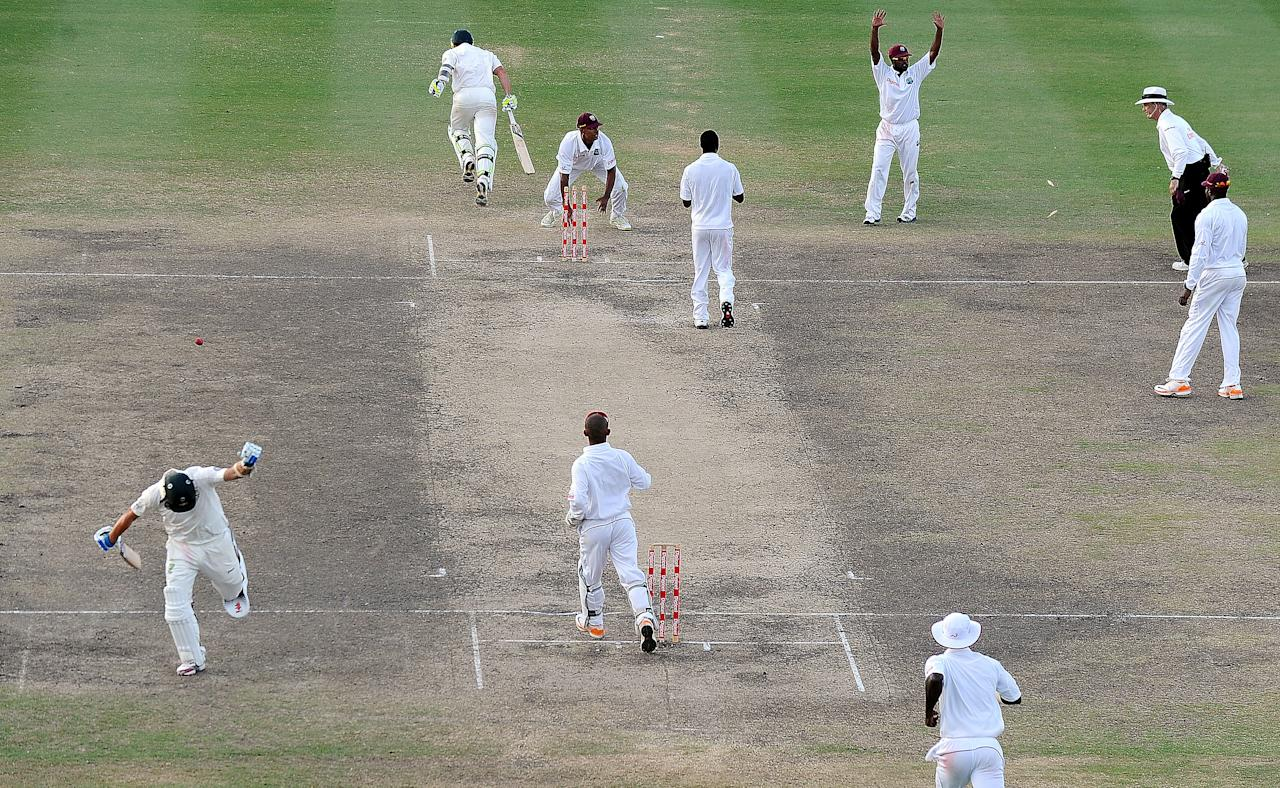 Australian cricketers Ryan Harris (L-bottom) and Ben Hilfenhaus (top-L) take a run to win during the final day of the first-of-three Test matches between Australia and West Indies at the Kensington Oval stadium in Bridgetown on April 11, 2012. Australia defeated West Indies by 3 wickets. AFP PHOTO/Jewel Samad (Photo credit should read JEWEL SAMAD/AFP/Getty Images)