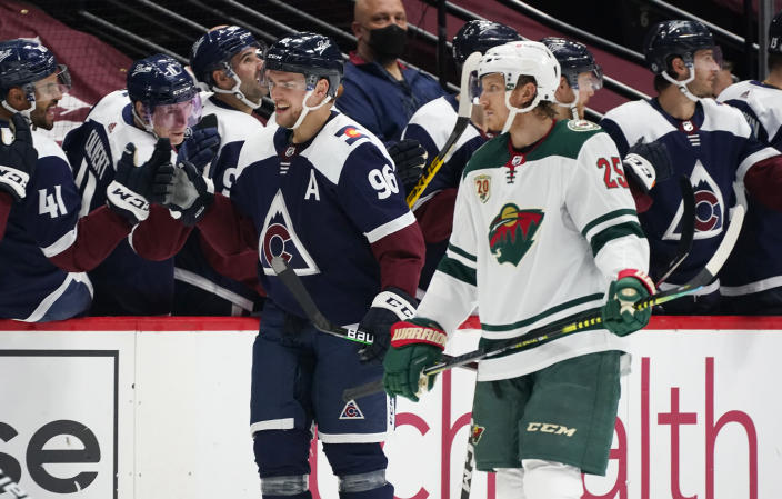 Colorado Avalanche right wing Mikko Rantanen, front left, smiles as he is congratulated while passing the team after scoring a goal as Minnesota Wild defenseman Jonas Brodin looks on in the second period of an NHL hockey game Saturday, March 20, 2021, in Denver. (AP Photo/David Zalubowski)
