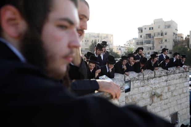 Ultra-Orthodox men watch Gestetner's funeral. While the victim was born in Montreal, he lived most recently near Monsey, N.Y. (Ariel Schalit/The Associated Press - image credit)