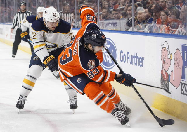 Buffalo Sabres' Johan Larsson (22) chases Edmonton Oilers' Matthew Benning (83) during first period NHL hockey action in Edmonton, Alberta, on Monday, Jan. 14, 2019. (Jason Franson/The Canadian Press via AP)