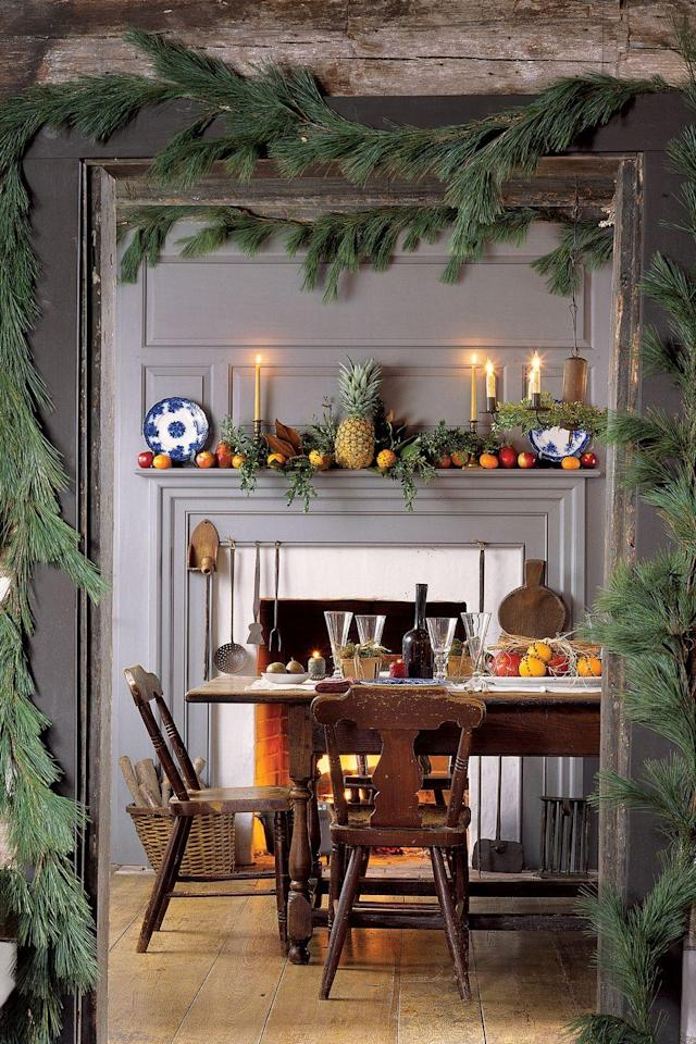 """<p>Evocative and soothing, candlelight creates the right ambience for the holidays. Lit candles are more than decorative objects, highlighting seasonal festivities and fostering a celebratory mood. Garlands around the door frame beckon guests into the room, and on the mantel sits a pineapple, an early-American symbol of hospitality.</p><p><a href=""""https://www.amazon.com/s/ref=nb_sb_noss?url=search-alias%3Dgarden&field-keywords=christmas+garland"""" rel=""""nofollow noopener"""" target=""""_blank"""" data-ylk=""""slk:SHOP GARLAND"""" class=""""link rapid-noclick-resp"""">SHOP GARLAND</a><br></p>"""