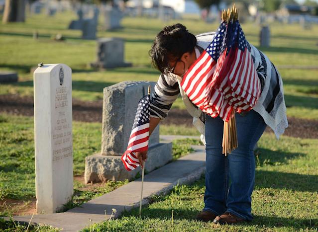 <p>Christine Galvan with Mission Messiah was one of many volunteers placing flags on veteran's graves on May 29, 2017, at the Ector County Cemetery in Odessa, Texas. (Photo: Mark Sterkel/Odessa American via AP) </p>