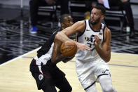 Utah Jazz center Rudy Gobert, right, loses the ball while driving to the basket as Los Angeles Clippers center Serge Ibaka defends during the first half of an NBA basketball game in Los Angeles, Friday, Feb. 19, 2021. (AP Photo/Kelvin Kuo)