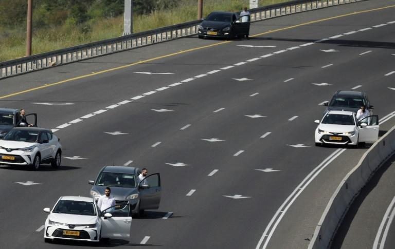 Israelis pause by their vehicles on the main highway leading to Jerusalem on April 8 as sirens wail across Israel for two minutes marking the annual day of remembrance for the six million Jewish victims of the Nazi genocide