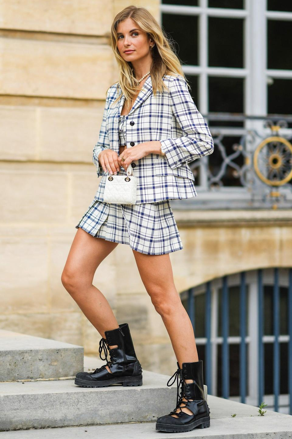 """A menswear-inspired look doesn't have to include trousers — as evidenced by Xenia Adonts' plaid mini skirt number. <span class=""""copyright"""">Photo: Edward Berthelot/Getty Images.</span>"""