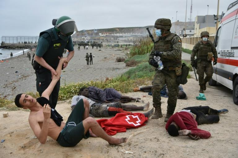 A Spanish Civil Guard officer holds a migrant who arrived swimming at the Spanish enclave of Ceuta