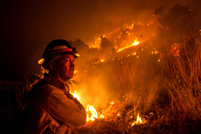 "A firefighter watches the Bobcat Fire burning on hillsides near Monrovia Canyon Park in Monrovia, California on September 15, 2020. - A major fire that has been raging outside Los Angeles for more than a week threatened to engulf a historic observatory and billion-dollar broadcast towers on September 15 as firefighters struggled to contain the flames. The so-called Bobcat Fire was within 500 feet (150 meters) from the 116-year-old Mt. Wilson Observatory, the US Forest Service said in a tweet, while fire officials said crews were in place ""ready to receive the fire."" (Photo by RINGO CHIU / AFP) (Photo by RINGO CHIU/AFP via Getty Images)"
