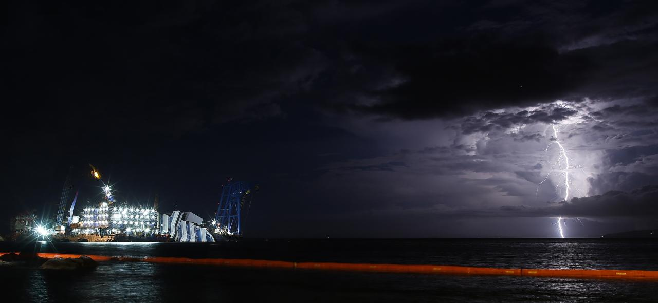 A lightning storm is pictured over the sea near the capsized cruise liner Costa Concordia, outside Giglio harbour September 15, 2013. REUTERS/Tony Gentile (ITALY - Tags: DISASTER TPX IMAGES OF THE DAY MARITIME)