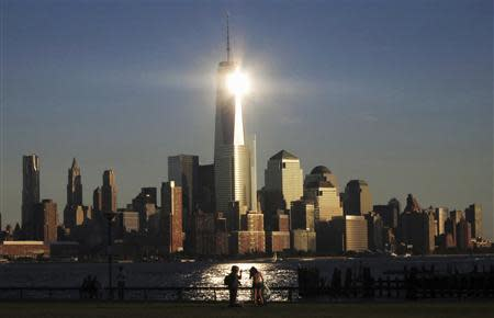 The sun reflects off New York's One World Trade Center as people stand in a park in Hoboken, New Jersey in this file photo
