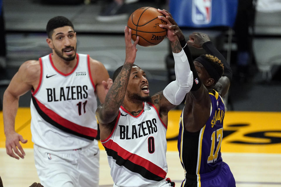 Los Angeles Lakers guard Dennis Schroder (17) blocks a shot by Portland Trail Blazers guard Damian Lillard (0) during the first half of an NBA basketball game Friday, Feb. 26, 2021, in Los Angeles. (AP Photo/Mark J. Terrill)