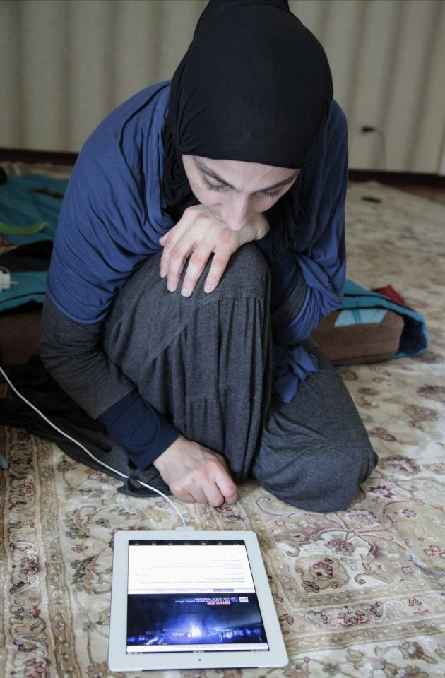Zubeidat Tsarnaeva, mother of the two Boston bombing suspects, shows videos on an iPad she says show her sons could not have been involved in last month's Boston Marathon bombings in Makhachkala, regional capital of Dagestan, Russia, Thursday, May 30, 2013. Authorities accuse Tamerlan Tsarnaev, who was slain in a shootout with police, and his younger brother Dzhokhar of organizing the attacks, which killed three. (AP Photo/Musa Sadulayev)